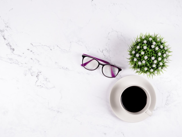 Verres à tasse à café et vase à fleurs sur fond de marbre blanc vue de dessus espace copie