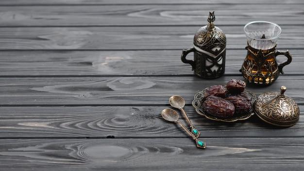 Verres à thé arabes turcs traditionnels et dates séchées avec des cuillères sur une table en bois
