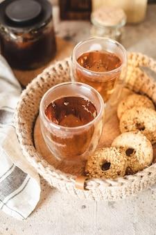 Verres de thé chaud dans un panier de jute avec des biscuits close up