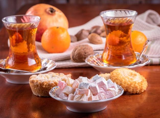Verres de thé et les loukoums sur une table avec des fruits, des noix et des biscuits