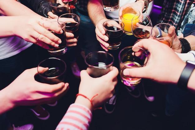 Verres tintants avec alcool et grillage, fête. félicitations à l'événement. amis de fête joyeux.