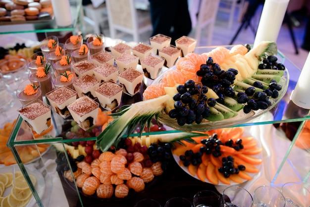 Verres avec tiramisu et plat avec des fruits sur une boîte en verre