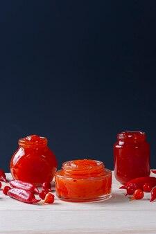 Verres transparents de confiture de poivre sur table en bois. espace pour le texte