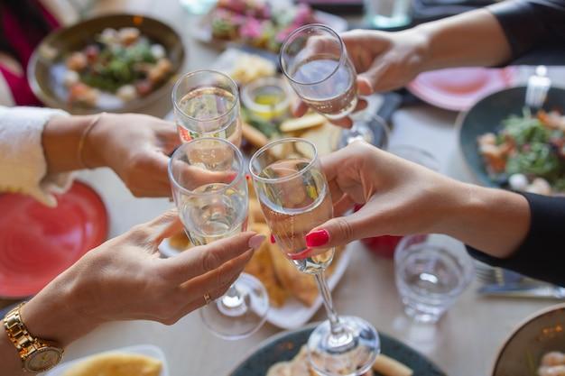 Verres trinquant avec de l'alcool et grillage, fête.