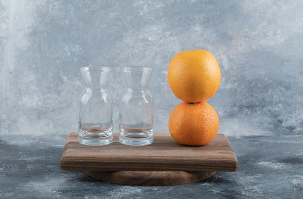Verres vides et oranges mûres sur planche de bois.