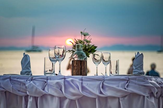 Des verres vides sont sur la table servie dans le contexte d'un coucher de soleil sur la mer sur une plage de sable