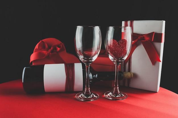 Les verres à vin avec un cœur à l'intérieur un cadeau et une boîte de chocolats
