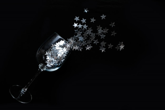 Verres à vin avec des confettis étoiles argentées sur fond noir. lay plat, vue de dessus.