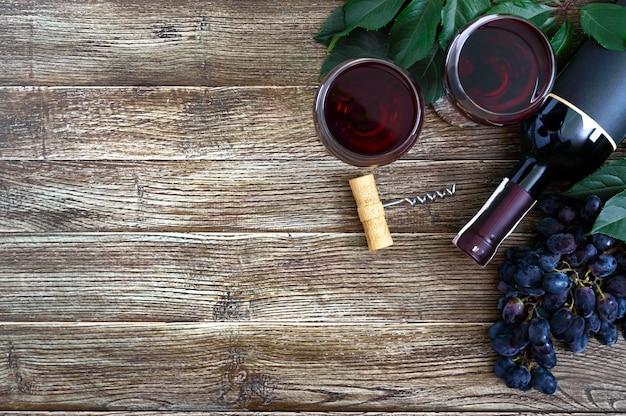 Verres à vin avec du vin rouge, bouteille, tire-bouchon, raisins bleus, feuilles sur une table en bois.