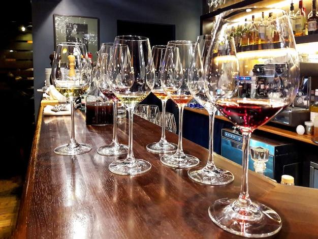 Verres de vin d'élite au bar dans un intérieur sombre.