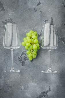 Verres à vin avec ensemble de raisins, sur table en pierre grise, vue de dessus à plat