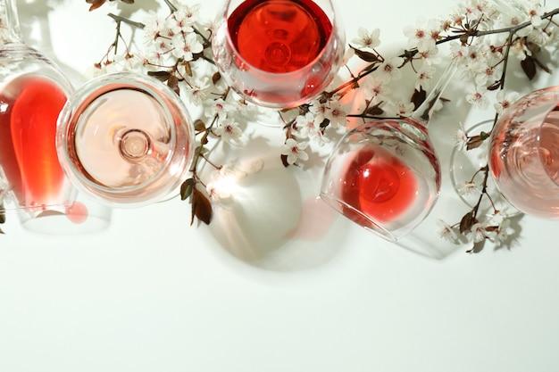 Verres de vin et fleurs de cerisier sur fond blanc