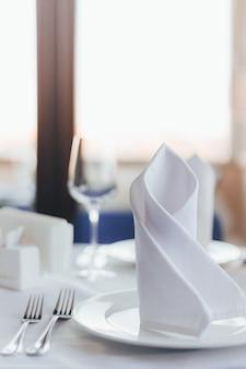 Verres à vin, fourchettes, cuillères, serviettes de table sur un fond clair flou