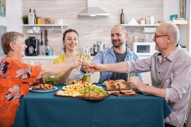 Verres à vin en hausse de famille heureuse pendant le déjeuner. grillage avec du vin blanc tout en dînant dans la cuisine. pommes de terre assaisonnées savoureuses.