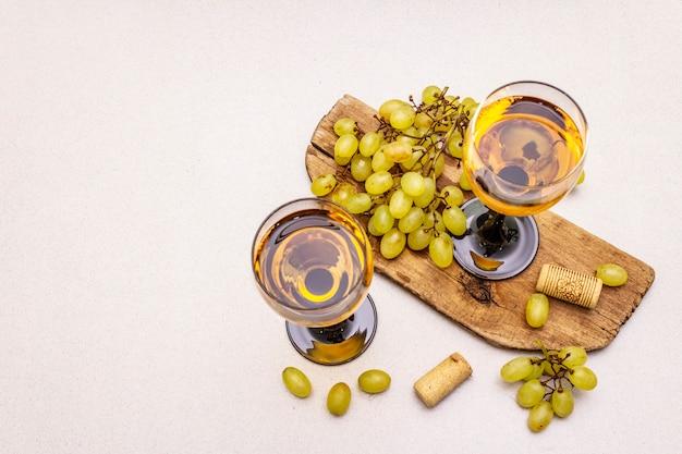 Verres à vin, raisins frais et bouchons sur planche à découper en bois