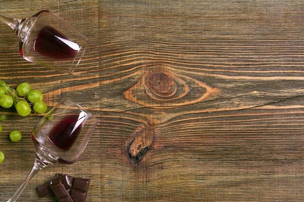 Verres de vin et raisins mûrs isolés sur une table en bois