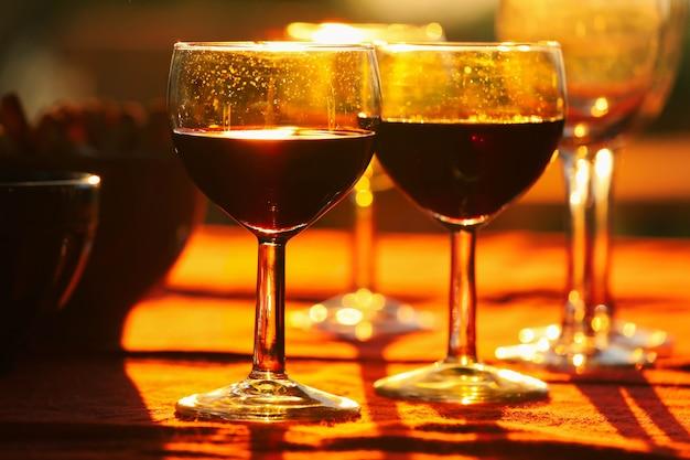 Verres à vin rouge sur table avec fond de collations pendant le coucher du soleil