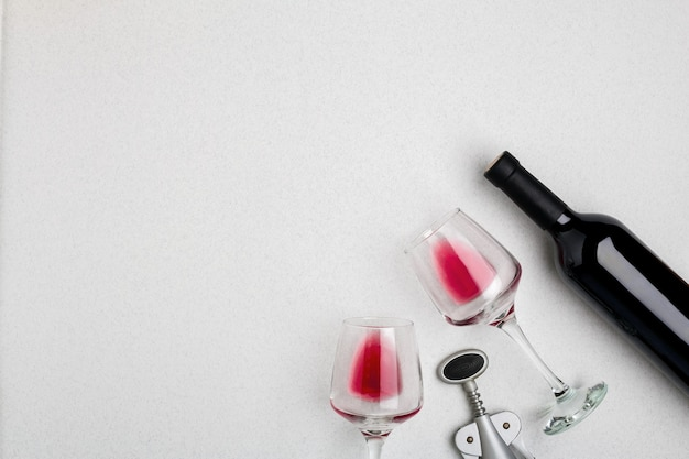 Verres à vin et tire-bouchon sur fond blanc vue de dessus