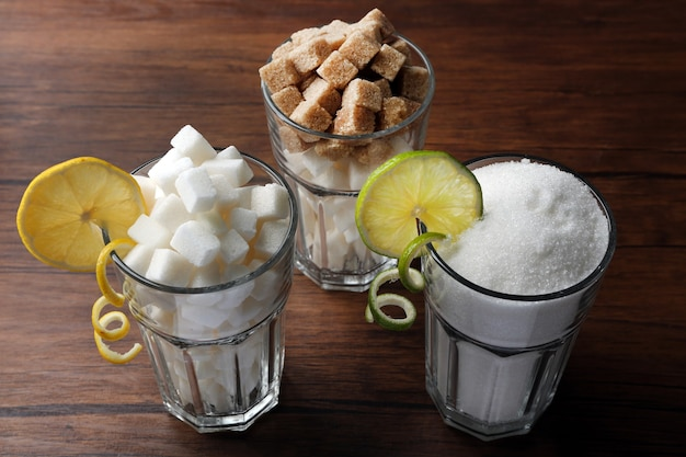 Verres à whisky avec sucre granulé et en morceaux sur table en bois