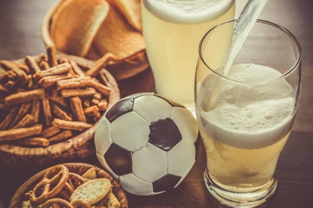 Verser la bière dans un verre avec des collations et du football