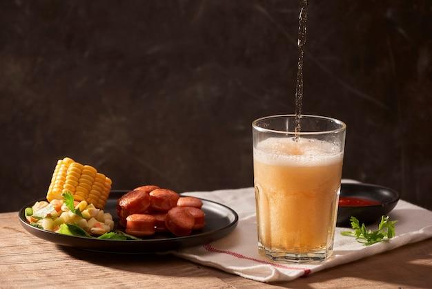 Verser de la bière dans un verre avec des saucisses, du ketchup, du maïs et de la salade sur une table en bois