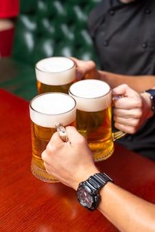 Verser de la bière debout au comptoir du bar grillant une grande bière artisanale au pub