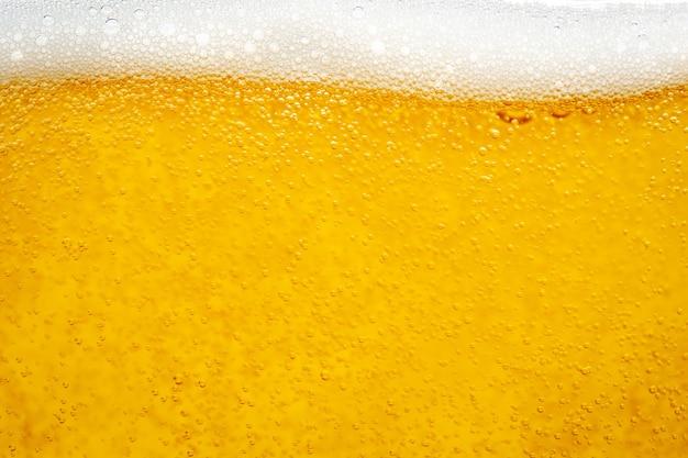 Verser la bière avec de la mousse à bulles dans le verre pour le fond et le design.