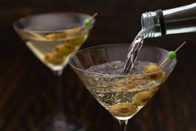 Verser des boissons alcoolisées de la bouteille dans le verre contre une table en bois.