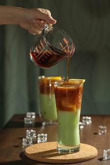 Verser un café infusé froid sur un latte au thé vert matcha