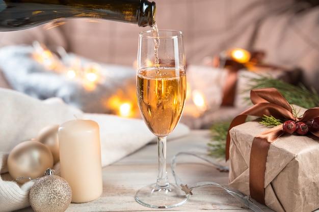 Verser le champagne dans un verre sur un fond de noël.