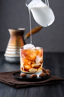 Verser la crème dans le café glacé