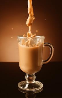 Verser du café avec du lait dans une tasse en verre à l'obscurité