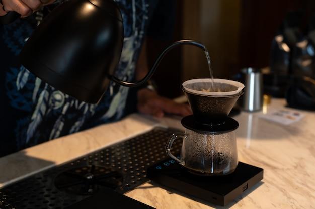 Verser du café avec de l'eau chaude d'une bouilloire en gros plan