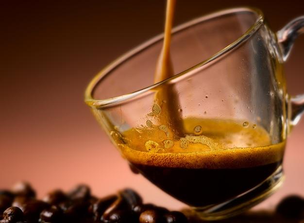 Verser du café sur une tasse en verre