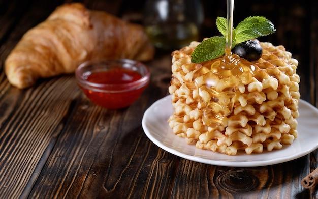 Verser du miel ou du sirop sur une pile de gaufres fraîchement préparées, décorées de myrtilles et de menthe sur une plaque blanche, une délicieuse pâtisserie maison pour le petit-déjeuner sur une table en bois ou un fond rustique