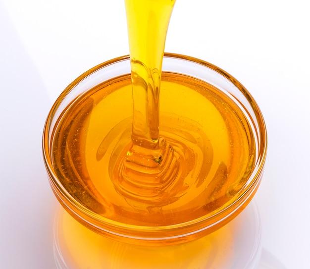Verser du miel sur une surface blanche