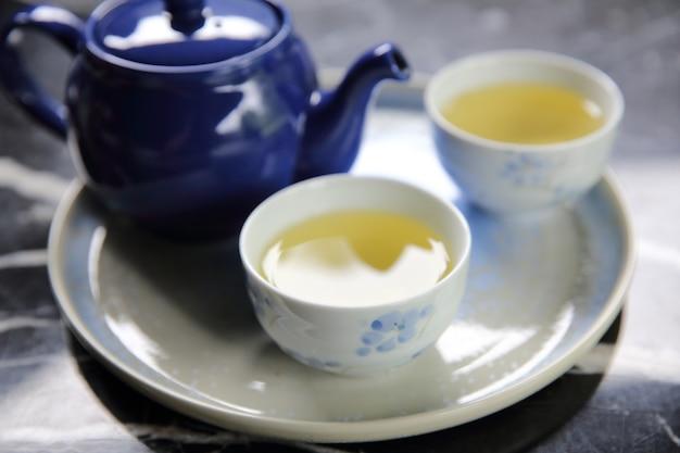 Verser du thé dans une tasse de thé en gros plan chinois et japonais boire