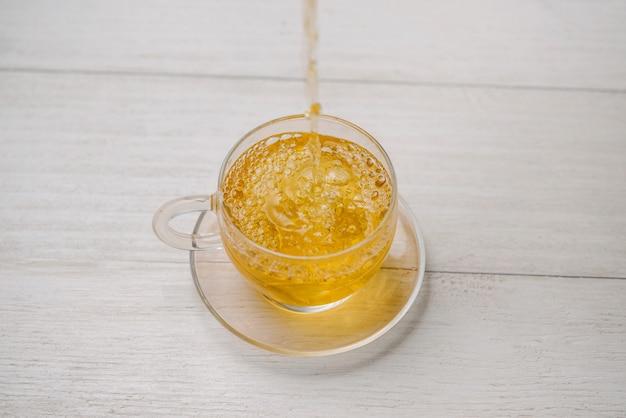 Verser du thé. tasse de thé chaud et feuille de thé sur la table en bois