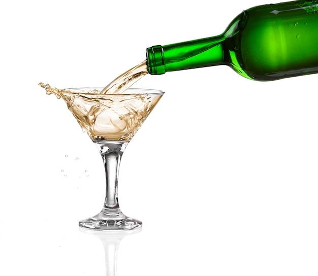 Verser du vin blanc de la bouteille le verre sur fond blanc