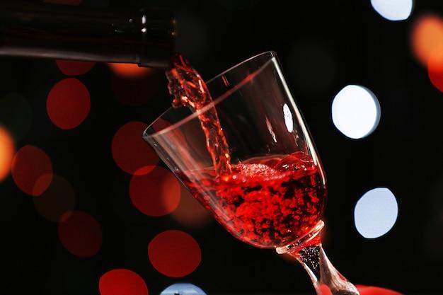 Verser du vin dans du verre sur une surface lumineuse