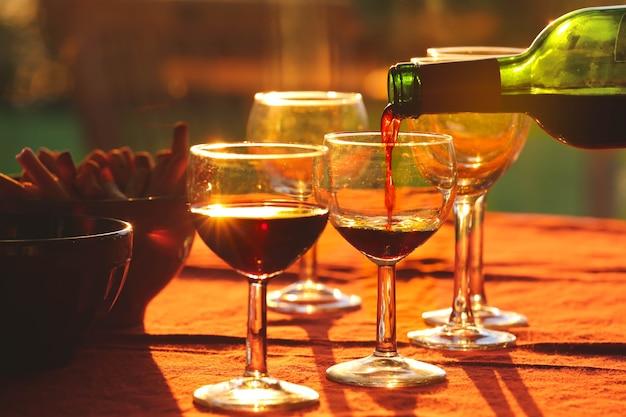 Verser du vin rouge de la bouteille dans des verres sur une table avec des collations en arrière-plan pendant le coucher du soleil