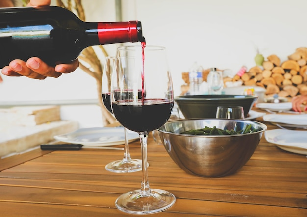 Verser du vin rouge de la bouteille dans des verres sur une table avec un fond de nourriture