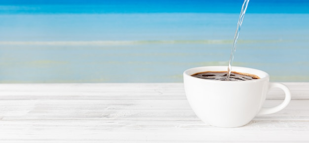 Verser de l'eau chaude dans une tasse de café sur une table en bois blanc avec un fond de mer bleu vif