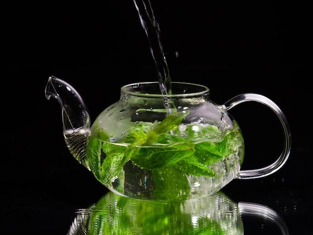 Verser de l'eau chaude dans une théière en verre sur fond noir thé à la menthe verte tisane et sain