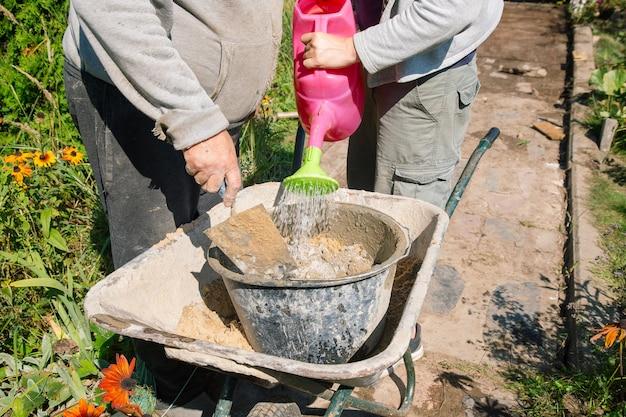 Verser de l'eau dans un mélange de ciment pour créer du ciment pour couler des chemins dans un jardin