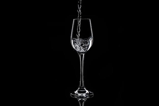 Verser de l'eau dans le verre à l'obscurité. silhouette isolée