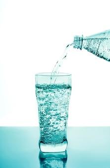 Verser de l'eau fraîche dans du verre à partir d'une bouteille en plastique sur fond bleu. verre d'eau potable fraîche avec fond bleu de bulles.