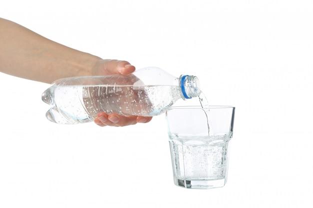 Verser de l'eau fraîche purifiée de la bouteille en verre, isolé sur blanc