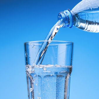 Verser de l'eau potable à partir d'une bouteille en plastique en verre, contre le ciel bleu avec des nuages.