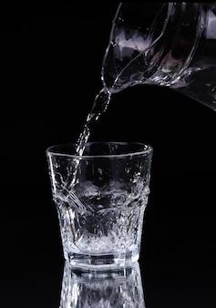 Verser de l'eau sur un verre sur fond noir